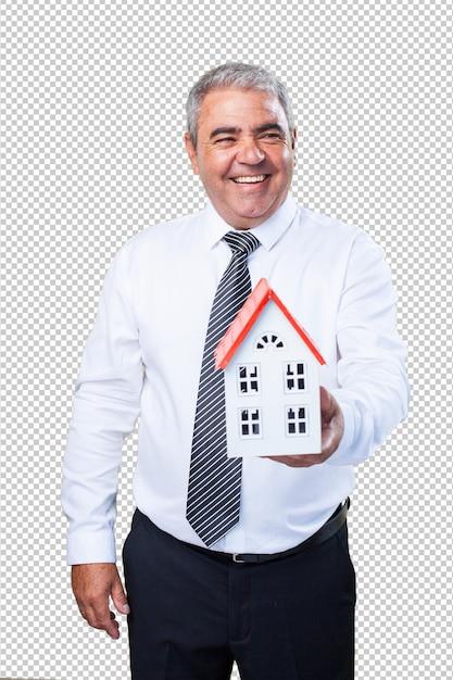 Heureux homme mûr tenant une maison PSD Premium
