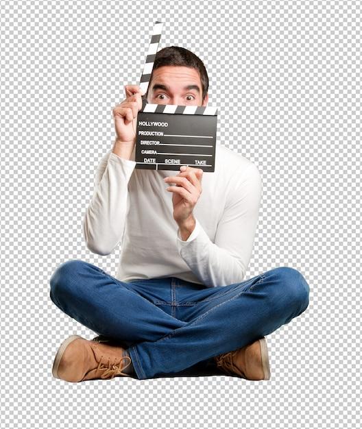 Heureux jeune homme assis à l'aide d'un clap PSD Premium