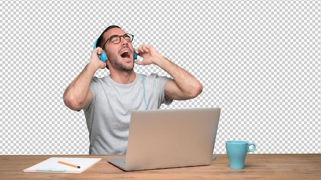 Heureux jeune homme assis à son bureau et utilisant un casque PSD Premium