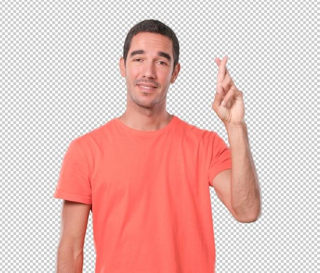 Heureux jeune homme avec le geste des doigts croisés PSD Premium