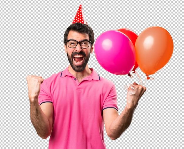 Heureux jeune homme tenant des ballons PSD Premium