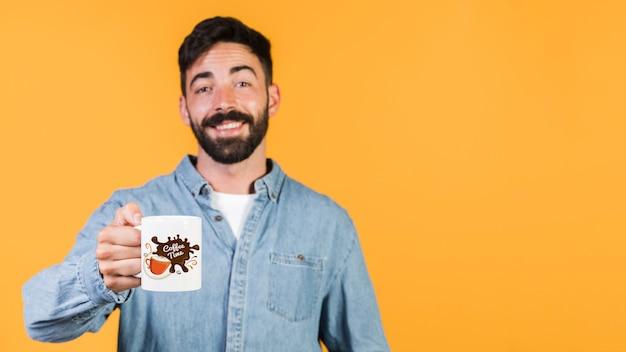 Heureux jeune homme tenant une tasse mock up Psd gratuit