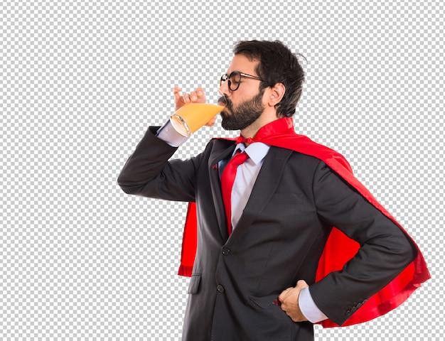 Homme D'affaires De Hipster Habillé Comme Un Super-héros Buvant Du Jus D'orange PSD Premium