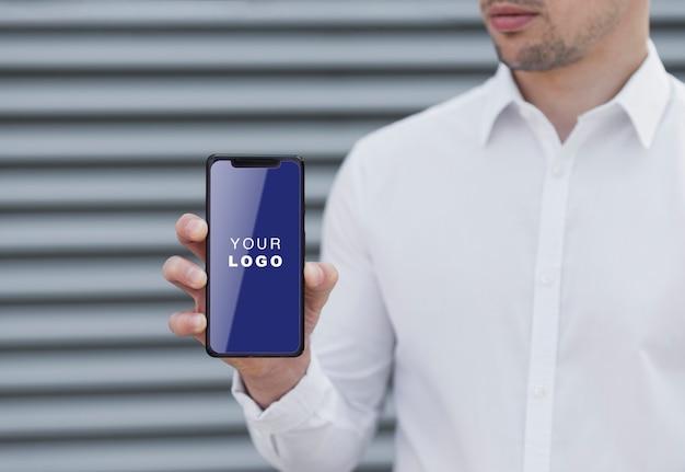 Homme D'affaires Tenant La Maquette D'un Smartphone Psd gratuit