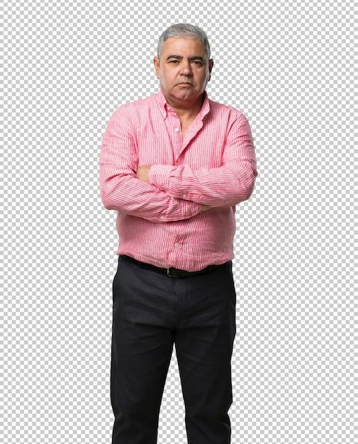 Homme d'âge moyen se croisant les bras, sérieux et imposant, confiant et faisant preuve de puissance PSD Premium