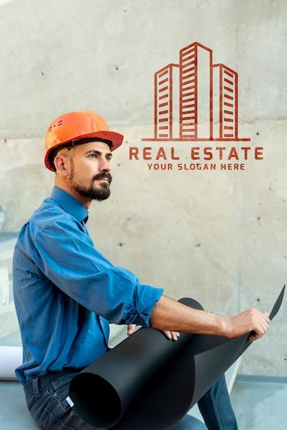 Homme agent latéral tenant des plans pour le nouveau bâtiment Psd gratuit