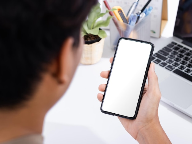 Homme à L'aide D'une Maquette D'écran De Smartphone Au Bureau Blanc PSD Premium