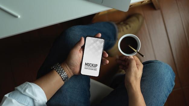 Homme à L'aide De Smartphone écran Blanc Maquette Et Tenant Une Tasse De Café Alors Qu'il était Assis Dans La Salle De Bureau PSD Premium
