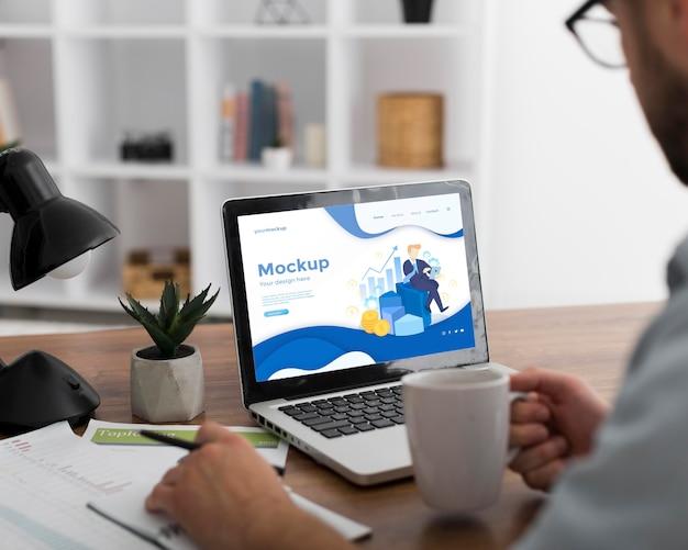 Homme Au Bureau Avec Maquette D'ordinateur Portable Psd gratuit