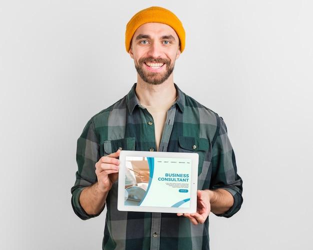 Homme Avec Chapeau D'hiver Tenant Une Tablette Avec La Page De Destination De L'entreprise Psd gratuit
