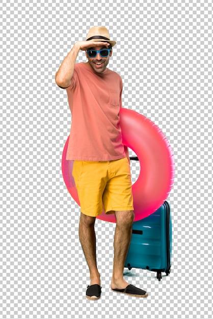 Homme avec chapeau et lunettes de soleil sur ses vacances d'été à la recherche de loin avec la main pour regarder quelque chose PSD Premium
