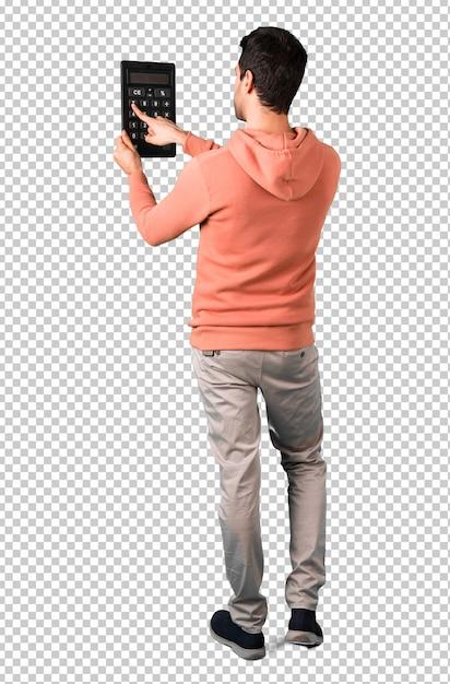 Homme dans un sweat-shirt rose tenant une calculatrice. machine à compter PSD Premium