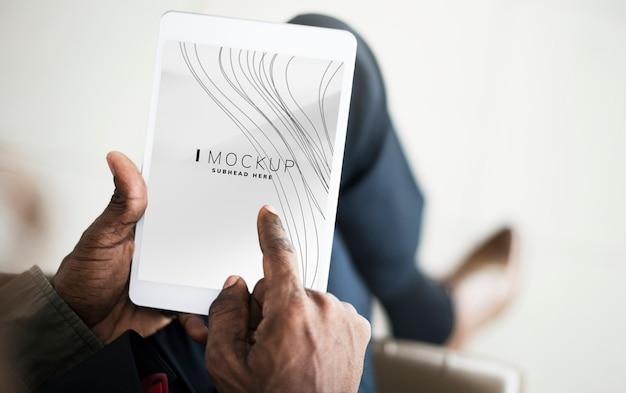 Homme jouant sur une tablette avec une maquette d'écran PSD Premium