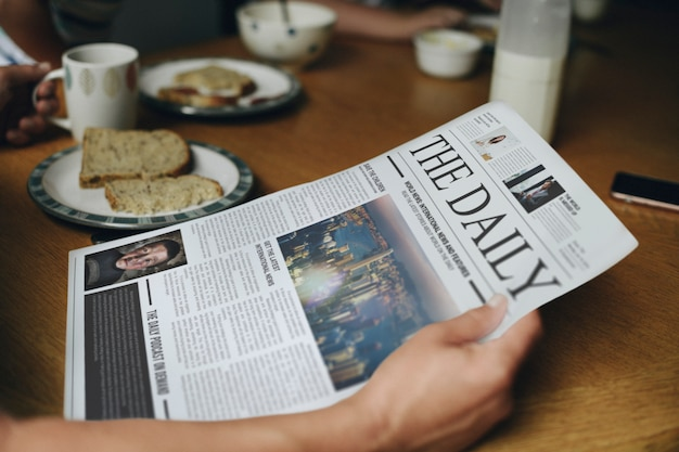 Homme lisant les nouvelles à la table du petit déjeuner Psd gratuit