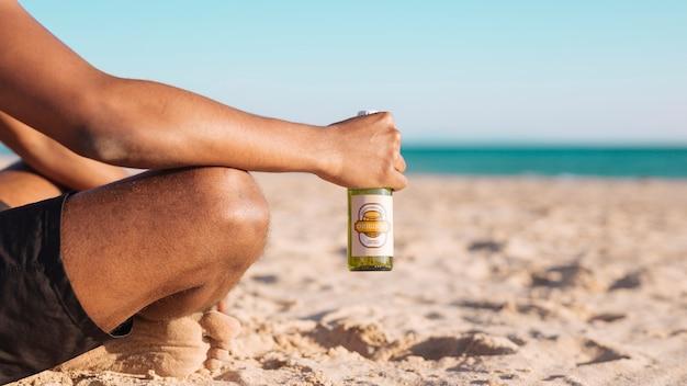 Homme avec maquette de bouteille de bière à la plage Psd gratuit