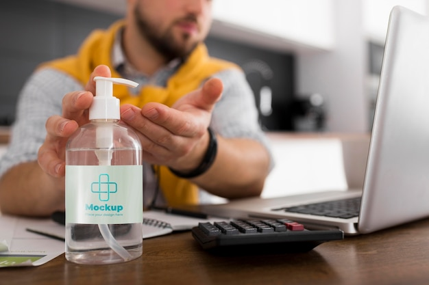 Homme Avec Ordinateur Portable à L'aide D'une Maquette De Désinfectant Psd gratuit