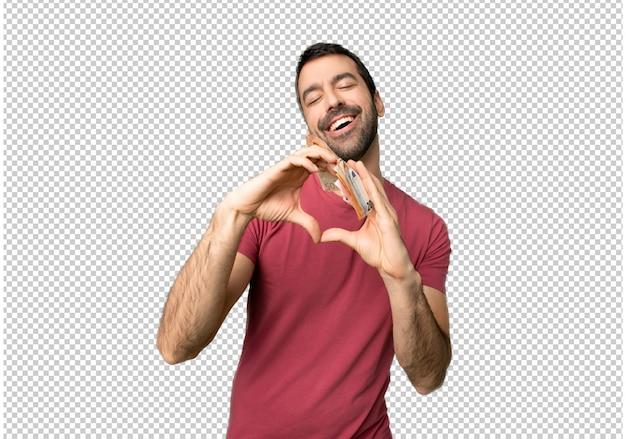 Homme prenant beaucoup d'argent faisant le symbole du coeur à la main PSD Premium