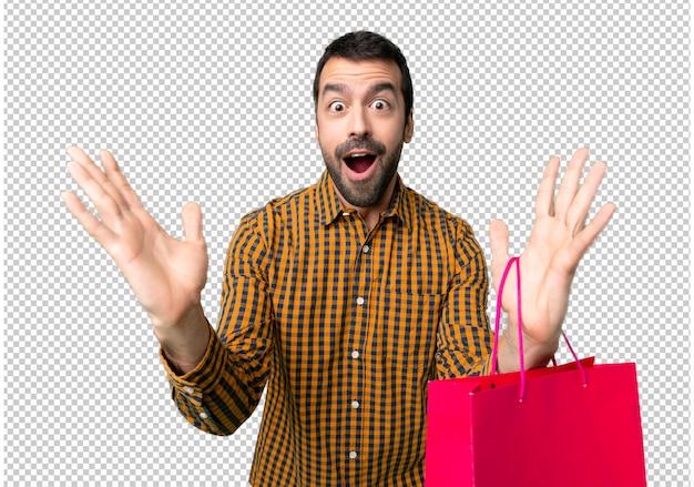 Homme avec des sacs à provisions avec une expression faciale surprise et choquée PSD Premium