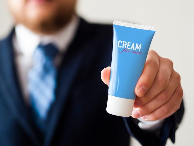 Homme Tenant Une Bouteille De Crème Pour Les Mains Pour La Maquette De L'homme Psd gratuit