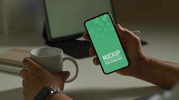 Homme Tenant Une Maquette De Smartphone Et Une Tasse De Café PSD Premium