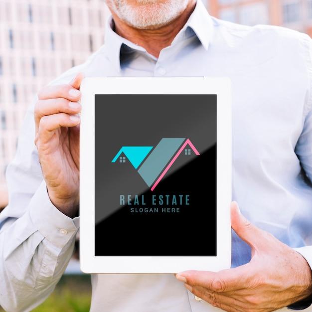 Homme tenant une maquette de tablette avec une entreprise immobilière Psd gratuit