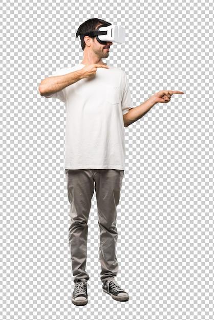 Homme utilisant des lunettes de réalité virtuelle pointant le doigt sur le côté PSD Premium
