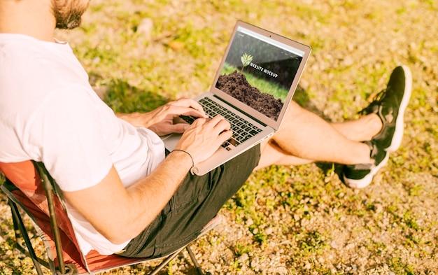 Homme utilisant une maquette de portable dans la nature Psd gratuit
