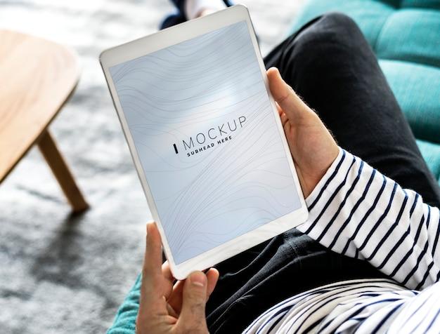 Homme utilisant une tablette avec une maquette d'écran PSD Premium
