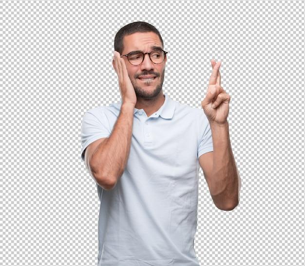 Inquiet jeune homme faisant un geste des doigts croisés PSD Premium