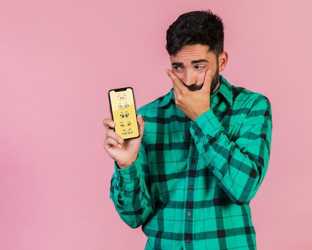 Inquiet, jeune homme tenant un téléphone portable maquette Psd gratuit