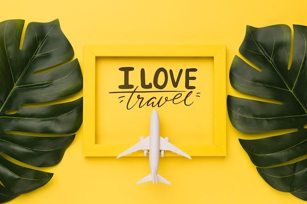 J'aime les voyages, lettrage citation sur cadre jaune avec avion et feuilles de palmier Psd gratuit