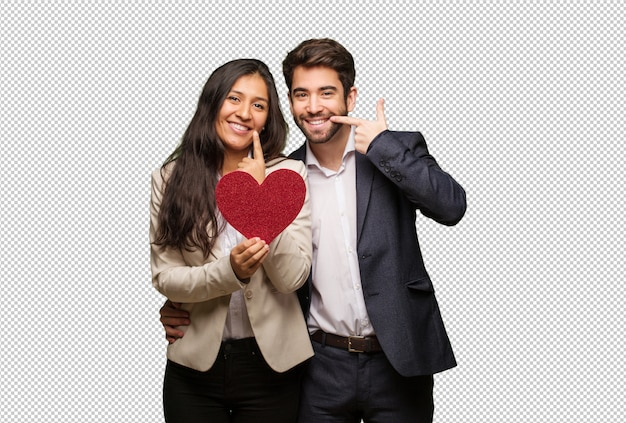 Jeune couple, dans, saint valentin, sourire, pointant bouche PSD Premium
