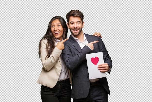 Jeune couple en saint valentin pointant sur le côté avec le doigt PSD Premium