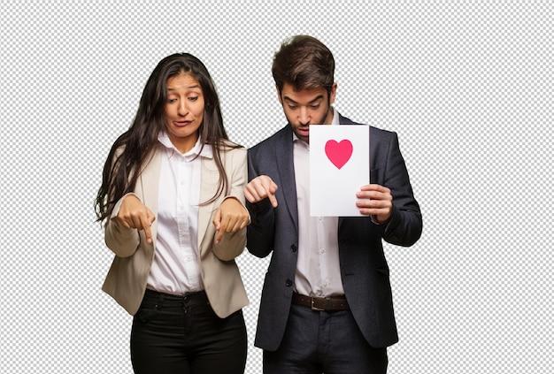 Jeune couple en saint valentin pointant vers le bas PSD Premium