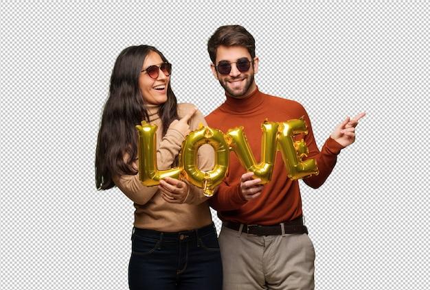 Jeune couple en saint valentin souriant et pointant sur le côté PSD Premium