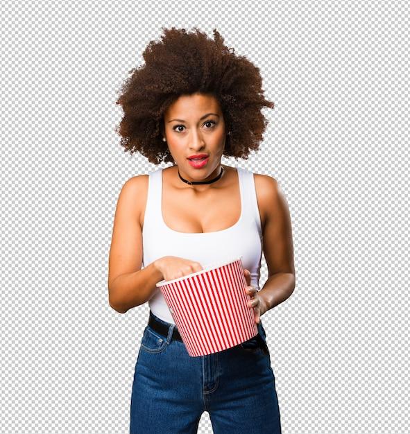Jeune femme noire tenant un seau de pop-corn PSD Premium