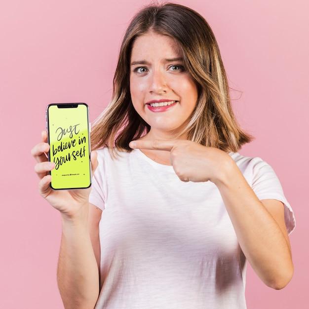 Jeune femme pointant un doigt sur une maquette de téléphone portable Psd gratuit
