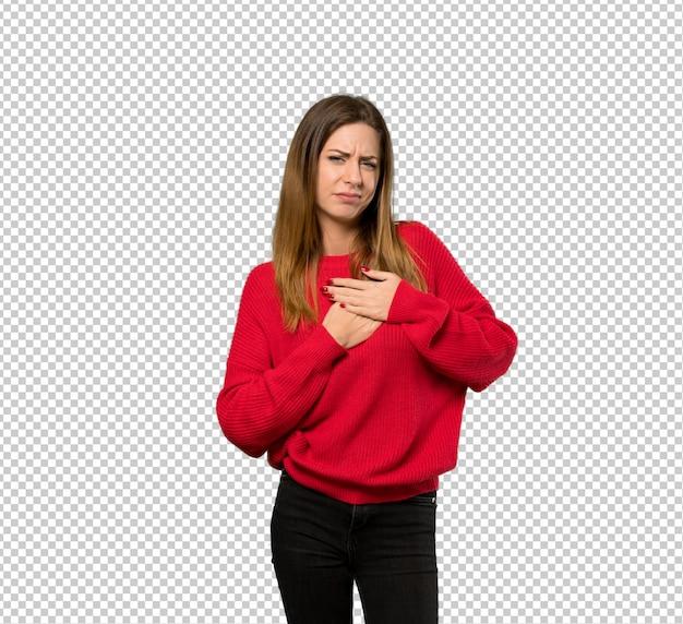 Jeune femme avec un pull rouge ayant une douleur au coeur PSD Premium