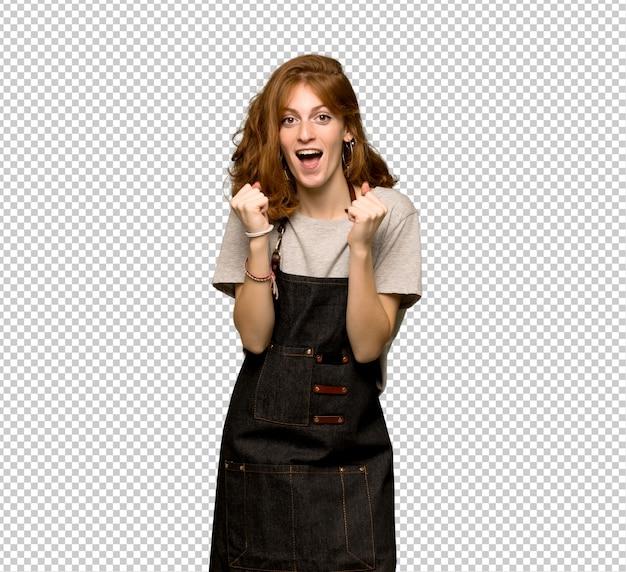 Jeune femme rousse avec tablier célébrant une victoire en position de vainqueur PSD Premium