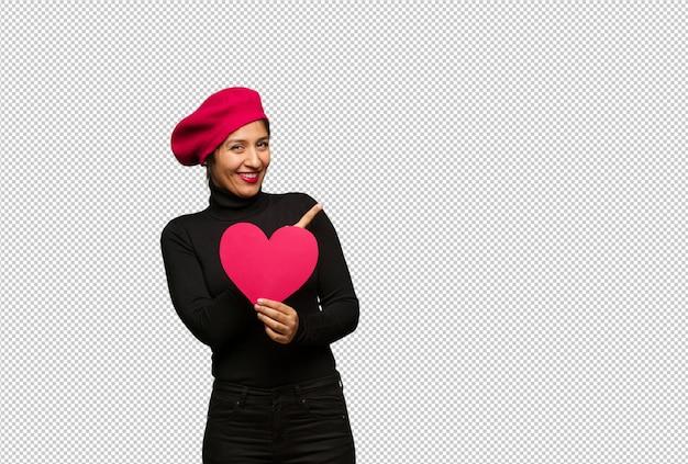 Jeune femme en saint valentin souriant et pointant sur le côté PSD Premium