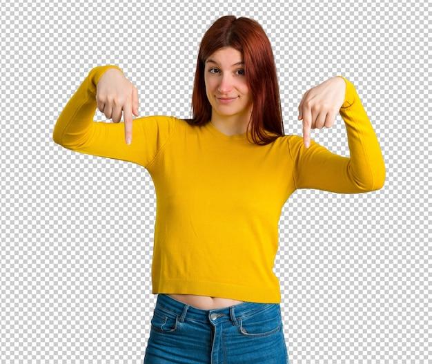 Jeune fille rousse avec pull jaune pointant vers le bas avec les doigts PSD Premium