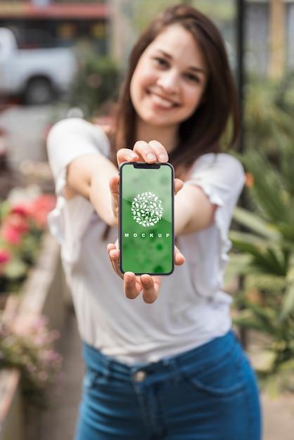 Jeune fille tenant une maquette de smartphone avec concept de jardinage Psd gratuit