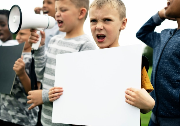 Jeune garçon montrant un papier vierge dans une manifestation PSD Premium
