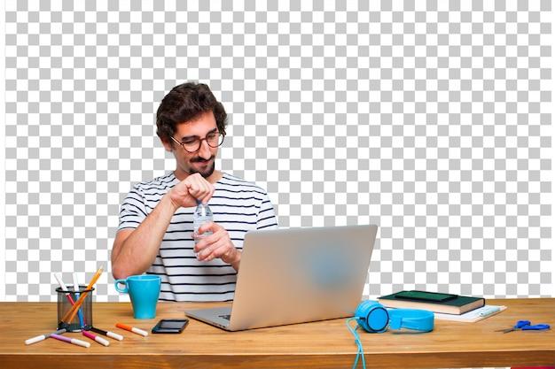 Jeune graphiste fou sur un bureau avec un ordinateur portable et une bouteille d'eau PSD Premium