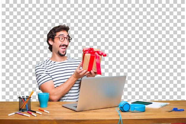 Jeune graphiste fou sur un bureau avec un ordinateur portable et avec le concept de boîte cadeau PSD Premium