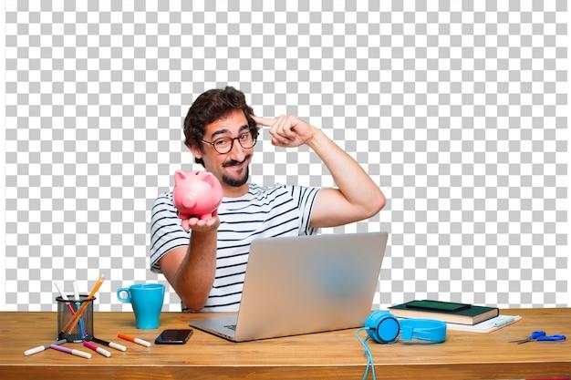 Jeune graphiste fou sur un bureau avec un ordinateur portable et une tirelire PSD Premium