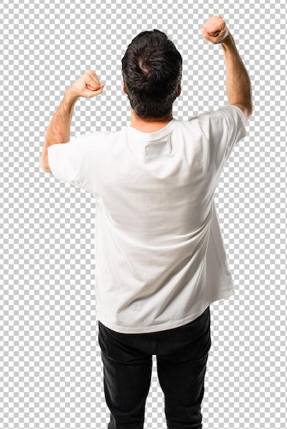 Jeune homme à la chemise blanche célébrant une victoire et surpris de réussir PSD Premium