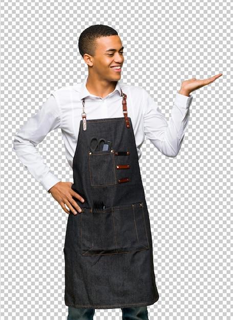 Jeune Homme De Coiffeur Afro-américain Tenant Une Surface Imaginaire Sur La Paume Pour Insérer Une Annonce PSD Premium