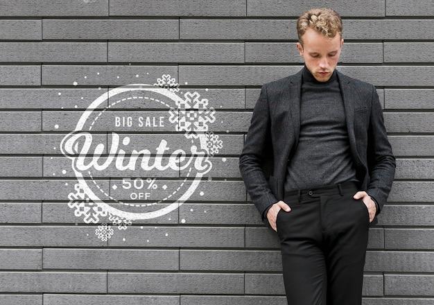 Jeune homme promouvant les soldes d'hiver Psd gratuit