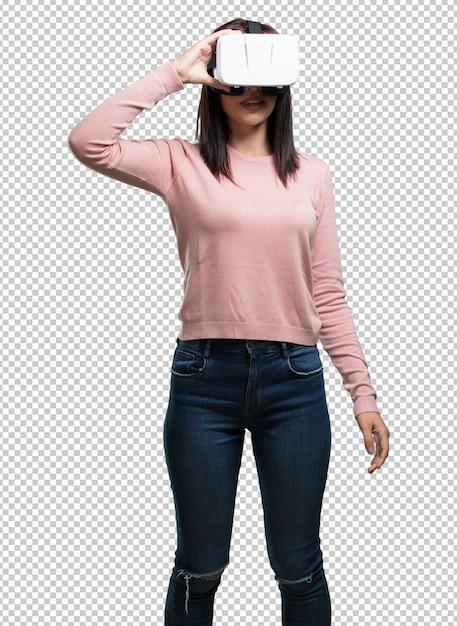 Jeune jolie femme excitée et divertie, jouant avec des lunettes de réalité virtuelle, explorant un monde fantastique, essayant de toucher quelque chose PSD Premium